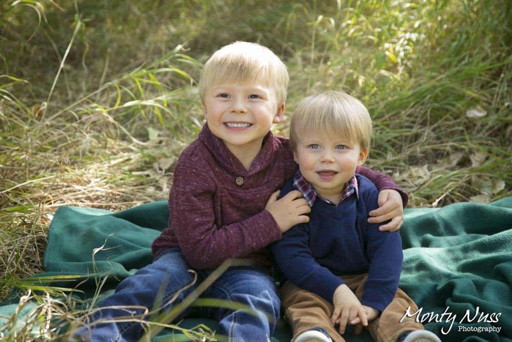 boys green blanket hug tall green grass burgundy navy plaid sweater