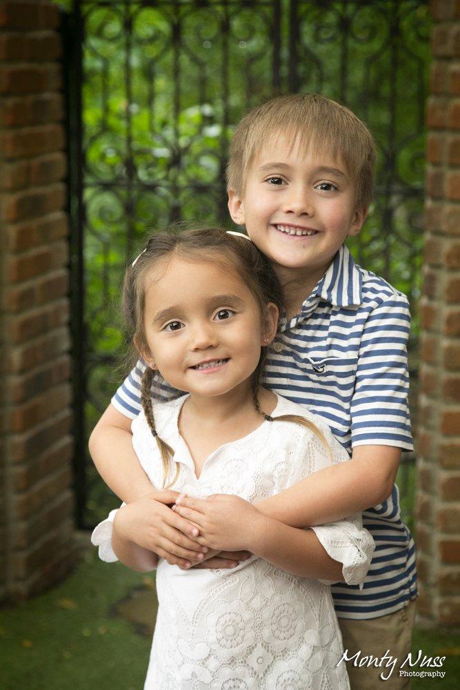 brick pillars outdoor studio photography siblings hug braids greenery black gate