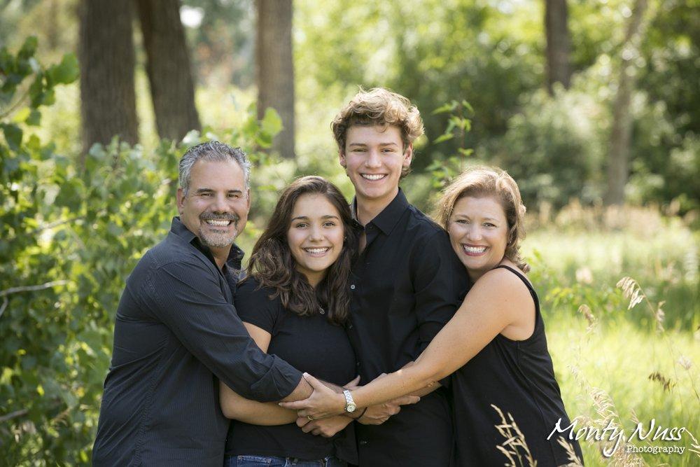 family hugging greenery park photographer